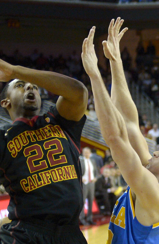 Southern California guard Byron Wesley, left, goes up for a shot as UCLA forward David Wear defends during the first half of an NCAA college basketball game, Saturday, Feb. 8, 2014, in Los Angeles