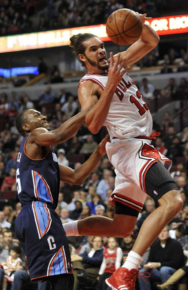 Chicago Bulls' Joakim Noah (13), goes up for a shot while being fouled by Charlotte Bobcats' Kemba Walker (15), during the third quarter of an NBA basketball game in Chicago, Monday, Nov. 18, 2013. Chicago won 86-81