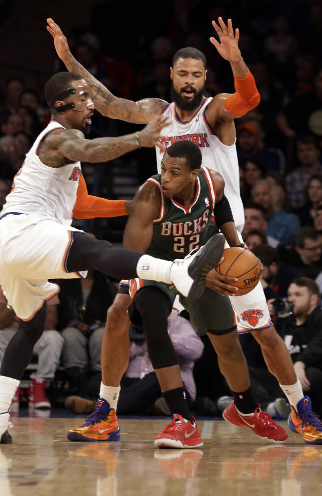 New York Knicks' J.R. Smith, left, and Tyson Chandler box in Milwaukee Bucks' Khris Middleton, center, in the second half of their NBA basketball game at New York's Madison Square Garden,  Saturday, March 15, 2014
