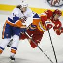 New York Islanders' Matt Martin, left, checks Calgary Flames' Mikael Backlund, from Sweden, during the first period of an NHL hockey game Friday, March 7, 2014, in Calgary, Alberta. (AP Photo/The Canadian Press, Jeff McIntosh)