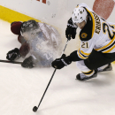 Boston Bruins right wing Loui Eriksson (21), of Sweden, turns to pick up the puck after knocking over Colorado Avalanche defenseman Zach Redmond in the first period of an NHL hockey game Wednesday, Jan. 21, 2015, in Denver The Associated Press