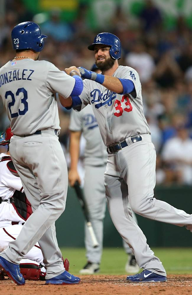 The Los Angeles Dodgers' Scott Van Slyke, right, is congratulated by teammate Adrian Gonzalez after Van Slyke hit a two-run home run in the Major League Baseball opening game between the Los Angeles Dodgers and Arizona Diamondbacks at the Sydney Cricket ground in Sydney, Saturday, March 22, 2014