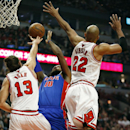 Detroit Pistons forward Greg Monroe (10) goes to the basket against Chicago Bulls center Joakim Noah (13) and forward Taj Gibson (22) during the first half of an NBA basketball game in Chicago, Saturday, Dec. 7, 2013 The Associated Press