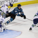San Jose Sharks' Tomas Hertl, center, of the Czech Republic, reaches for the puck while surrounded by Vancouver Canucks goalie Joacim Eriksson (32), of Sweden, defenseman Yannick Weber (6) and center Cal O'Reilly, right, during the second period of an NHL