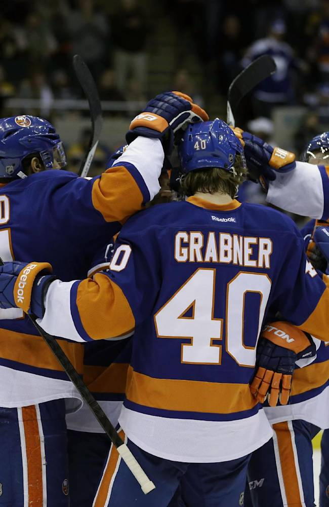 New York Islanders' Michael Grabner (40) celebrates his goal with teammates during the second period of the NHL hockey game against the Boston Bruins, Monday, Jan. 27, 2014, in Uniondale, New York