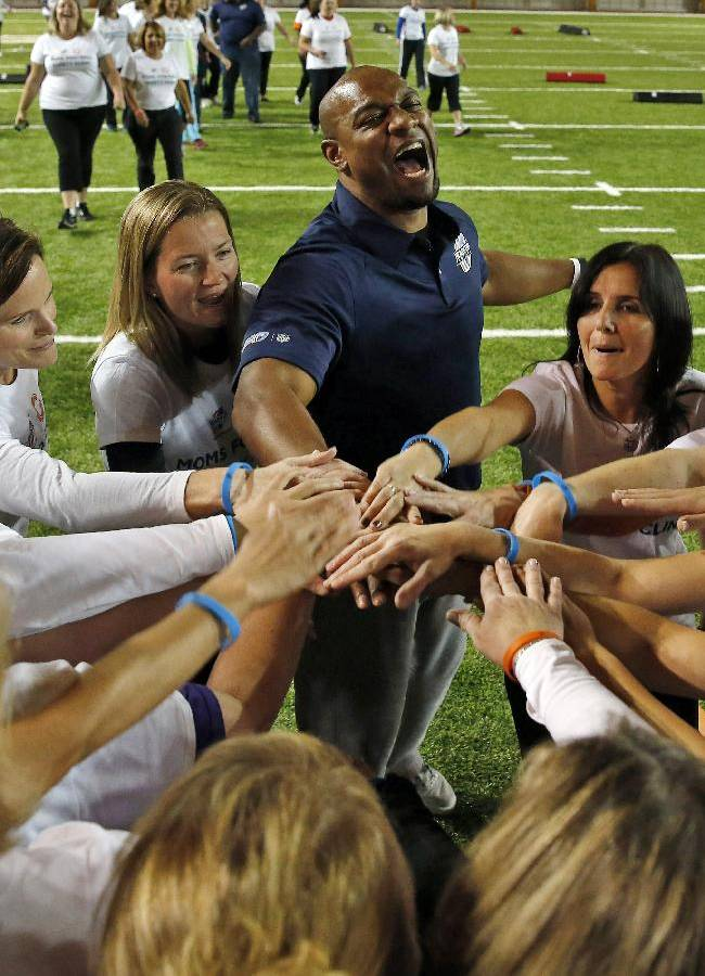 Jarrett Payton, center, rallies with participants during a safety clinic hosted by the NFL and the Chicago Bears for the mothers of youth football players on Tuesday, Oct. 29, 2013, at Halas Hall in Lake Forest, Ill