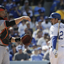 Los Angeles Dodgers' Adrian Gonzalez, right, looks at the umpire after striking out as San Francisco Giants catcher Buster Posey, left, throws the ball to pitcher David Huff during the fifth inning of a baseball game on Friday, April 4, 2014, in Los Angel