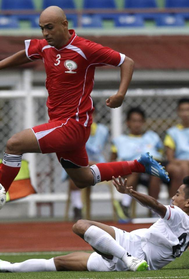 Myanmar's Soe Min Oo (25) and Palestine's Husam I.A. Abusalah (3) battle for ball during the Peace Cup 2014 friendly soccer match between Myanmar and Palestine at the Rizal Memorial Football Stadium Wednesday, Sept. 3, 2014 in Manila, Philippines. Myanmar beat Palestine 4-1 to advance to the finals