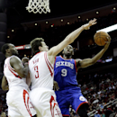 Philadelphia 76ers' James Anderson (9) drives to the basket around Houston Rockets' Omer Asik (3) and Jordan Hamilton, left, during the first half of an NBA basketball game on Thursday, March 27, 2014, in Houston The Associated Press