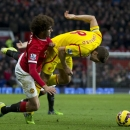 Manchester United's Marouane Fellaini, left, fights for the ball against Liverpool's Steven Gerrard during the English Premier League soccer match between Manchester United and Liverpool at Old Trafford Stadium, Manchester, England, Sunday Dec. 14, 2014