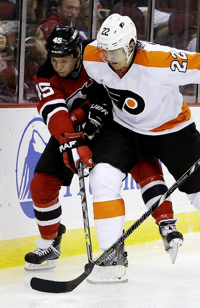 New Jersey Devils right wing Cam Janssen (45) and Philadelphia Flyers defenseman Luke Schenn (22) compete for the puck during the second period of an NHL preseason hockey game, Thursday, Sept. 26, 2013, in Newark, N.J