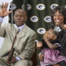 With his wife Betina and daughter Charity at his side, Green Packers all time leading receiver, Donald Driver, waves to fans during his retirement ceremony Wednesday, Feb. 6, 2013 at Lambeau Field in Green Bay, Wis. (AP Photo/Mike Roemer)