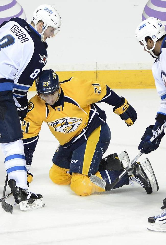 Winnipeg Jets defenseman Jacob Trouba (8) and Dustin Byfuglien (33) knock the puck away from Nashville Predators forward Simon Moser (21), of Switzerland, in the third period of an NHL hockey game on Saturday, March 1, 2014, in Nashville, Tenn. The Jets won 3-1