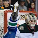 Minnesota Wild goalie Darcy Kuemper, right, reacts as Vancouver Canucks' Brad Richardson goes flying after being tripped up in front of the net during the first period of an NHL hockey game Friday, Feb. 28, 2014, in Vancouver, British Columbia The Associa