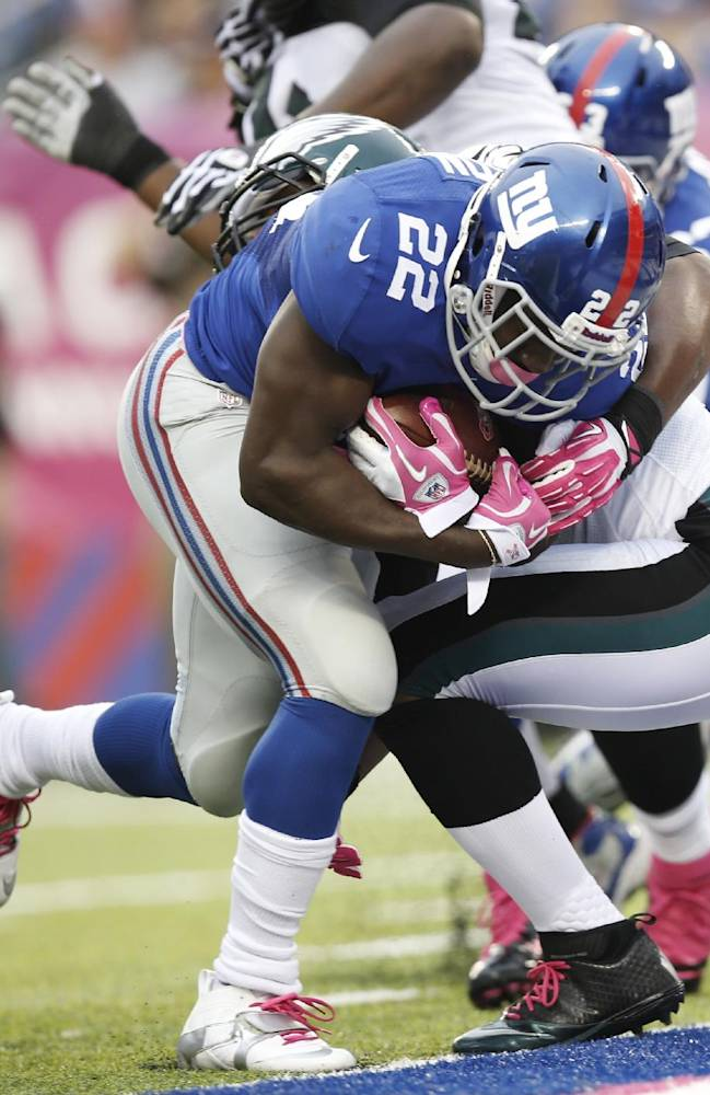 New York Giants' David Wilson (22) breaks a tackle by Philadelphia Eagles' DeMeco Ryans for a touchdown during the first half of an NFL football game Sunday, Oct. 6, 2013, in East Rutherford, N.J