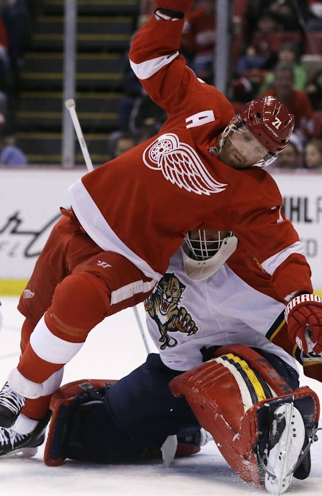 Detroit Red Wings right wing Daniel Cleary (71) falls over Florida Panthers goalie Tim Thomas (34) during the first period of an NHL hockey game in Detroit, Sunday, Jan. 26, 2014
