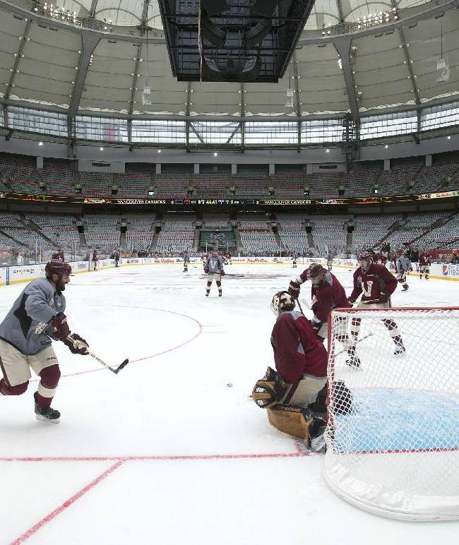 Vancouver Canucks' Jason Garrison, left, passes to Chris Higgins as goalie Roberto Luongo moves to make the save during practice for the NHL Heritage Classic hockey game in Vancouver, British Columbia, on Saturday, March 1, 2014. The Canucks are scheduled to play the Ottawa Senators on Sunday