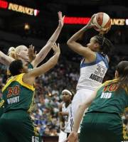 Minnesota Lynx guard Seimone Augustus (33) goes up to the basket against Seattle Storm forward Lauren Jackson, left rear, and guard Tanisha Wright (30) during the first half of Game 1 of the WNBA basketball first-round playoff series Friday, Sept. 28, 2012, in Minneapolis. (AP Photo/Stacy Bengs)