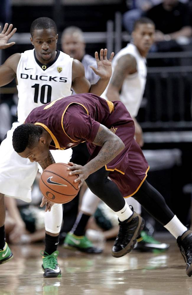 Arizona State guard Jahii Carson, right, loses his balance driving against Oregon guard Johnathan Loyd during the first half of an NCAA college basketball game in Eugene, Ore., Tuesday, March 4, 2014