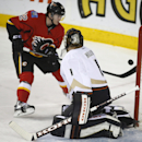 Anaheim Ducks goalie Jonas Hiller, right, from the Czech Republic, watches as Calgary Flames' Paul Byron tries to tip the puck past him during the first period of an NHL hockey game in Calgary, Alberta, Wednesday, March 26, 2014 The Associated Press