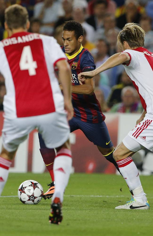 Barcelona's Neymar, center, shoots on goal as Ajax's Niklas Moisander, left, and Ajax's Christian Poulsen, right, try and block the shot  during the Champions League group H soccer match between Ajax Amsterdam and F.C. Barcelona on Wednesday, Sept. 18, 2013, at Camp Nou stadium in Barcelona, Spain