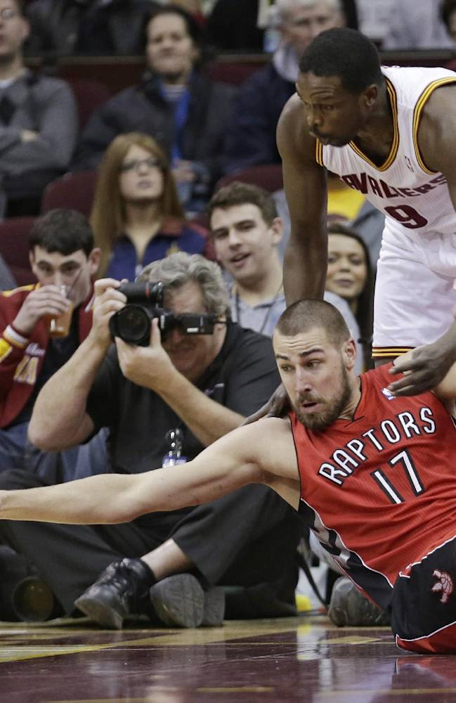 Toronto Raptors' Jonas Valanciunas (17), from Lithuania, stretches for the ball under pressure from Cleveland Cavaliers' Luol Deng, (9) from Sudan, during the first quarter of an NBA basketball game Tuesday, Feb. 25, 2014, in Cleveland