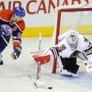 Chicago Blackhawks goalie Corey Crawford (50) sweeps the puck away from Edmonton Oilers' Ryan Smyth (94) during the third period of an NHL hockey game in Edmonton, Alberta, Monday, Nov. 25, 2013 The Associated Press