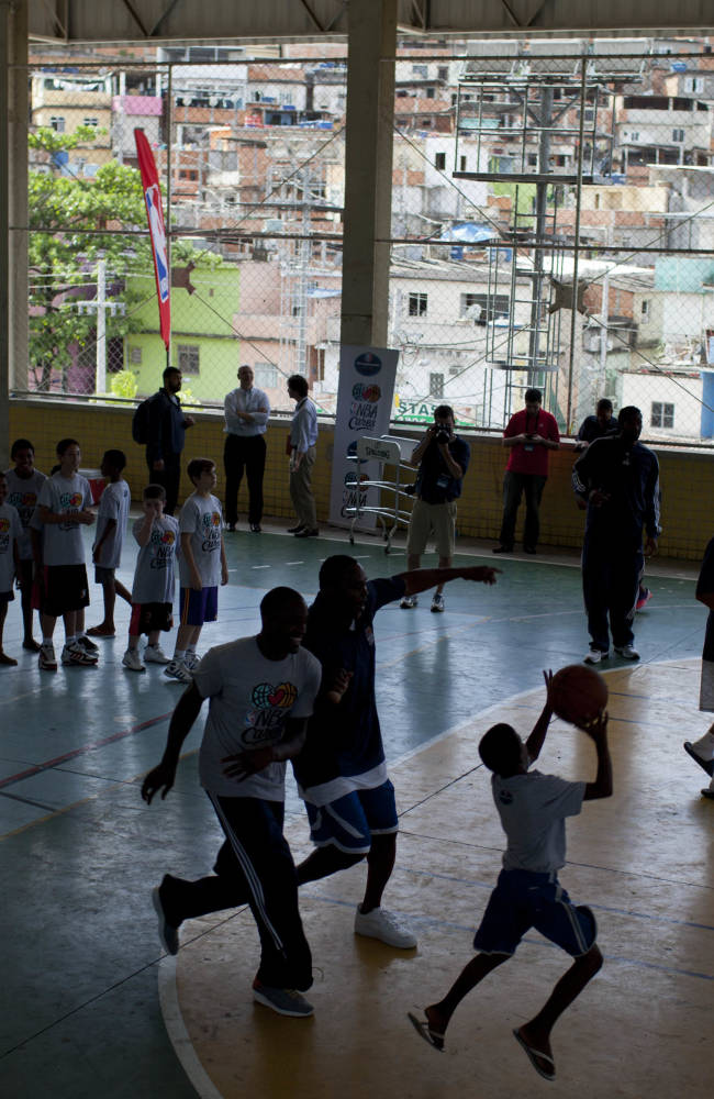 Children take part in a basketball clinic led by Washington Wizards players and former player Horace Grant at the Complexo do Alemao slum in Rio de Janeiro, Brazil, Friday, Oct. 11, 2013. Brazilian Nene Hilario led his teammates to the pacified shantytown in the city's north side. The Wizards are in Brazil preparing for NBA's first exhibition game in South America against the Chicago Bulls on Saturday