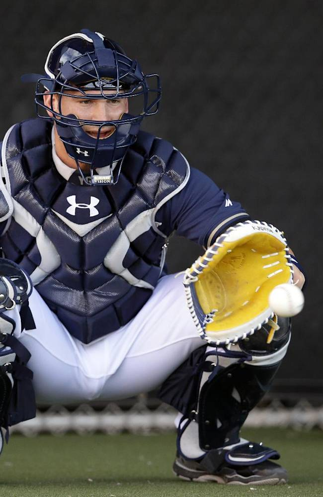 San Diego Padres catcher Yasmani Grandal takes a pitch as he catches a bullpen session during spring training baseball practice on Sunday, Feb. 16, 2014, in Peoria, Ariz
