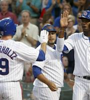 Chicago Cubs' Nate Schierholtz is greeted at home by teammate Dioner Navarro, center, and Junior Lake after hitting a three-run home run off Washington Nationals starting pitcher Jordan Zimmermann, also scoring Lake and Navarro, during the first inning of a baseball game, Monday, Aug. 19, 2013, in Chicago. (AP Photo/Charles Rex Arbogast)