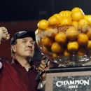 Florida State head coach Jim Fisher celebrates next to the Orange Bowl trophy after defeating Northern Illinois 31-10 at the Orange Bowl NCAA college football game, early Wednesday, Jan. 2, 2013, in Miami. (AP Photo/Alan Diaz)