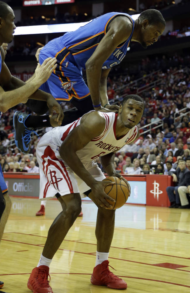 Oklahoma City Thunder's Kevin Durant, top, jumps on the back of Houston Rockets' Terrence Jones (6) as he fouls him during the third quarter of an NBA basketball game Thursday, Jan. 16, 2014, in Houston. The Thunder beat the Rockets 104-92