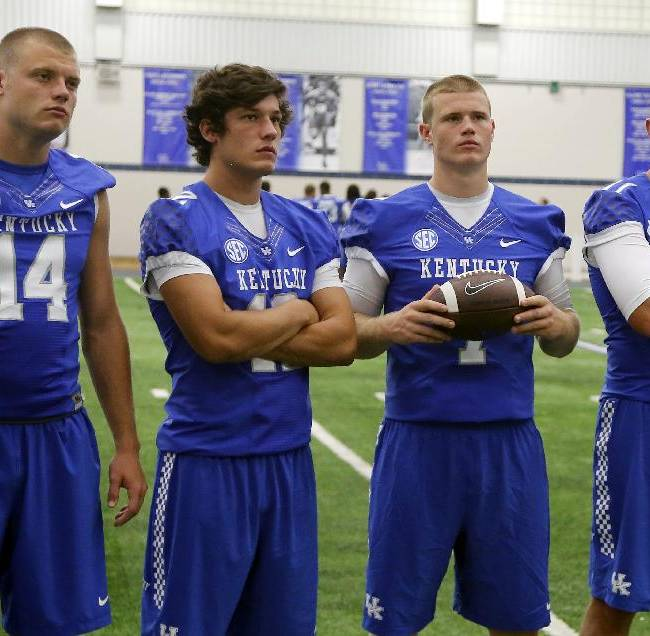 Kentucky starting quarterback hopefuls, from left, Patrick Towles, Reese Phillips, Drew Barker and Max Smith wait to have their photo taken during the team's NCAA college football media day, Friday, Aug. 8, 2014, in Lexington, Ky