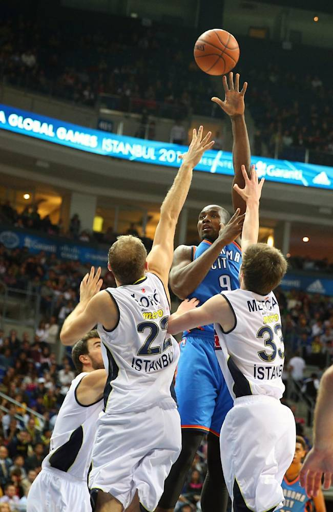 Oklahoma City Thunder's Serge Ibaka, top, goes for a basket as  Fenerbahce Ulker's players defend during a basketball game in Istanbul, Turkey, Saturday, Oct. 5, 2013. Oklahoma City Thunder has opened the preseason schedule with a game against five-time Turkish champion at the Ulker Sports Arena.(AP Photo)