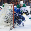 Vancouver Canucks' Derek Dorsett, centre, is checked into Dallas Stars' goalie Kari Lehtonen, of Finland, by Jason Demers, right, during the first period of an NHL hockey game in Vancouver, British Columbia, on Wednesday, Dec. 17, 2014 The Associated Pres