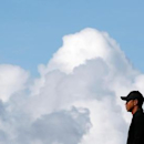 Tiger Woods of the U.S. stands on the 12th green during a practice round ahead of the British Open Championship at the Royal Liverpool Golf Club in Hoylake, northern England July 15, 2014.        REUTERS/Stefan Wermuth/File Photo - RTSIQOP