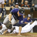 San Diego Padres' Xavier Nady slides in safely as Colorado Rockies relief pitcher Rex Brothers can't catch the throw from the catcher after a wild pitch in the eighth inning of a baseball game Monday, April 14, 2014, in San Diego. Two runs scored on the p