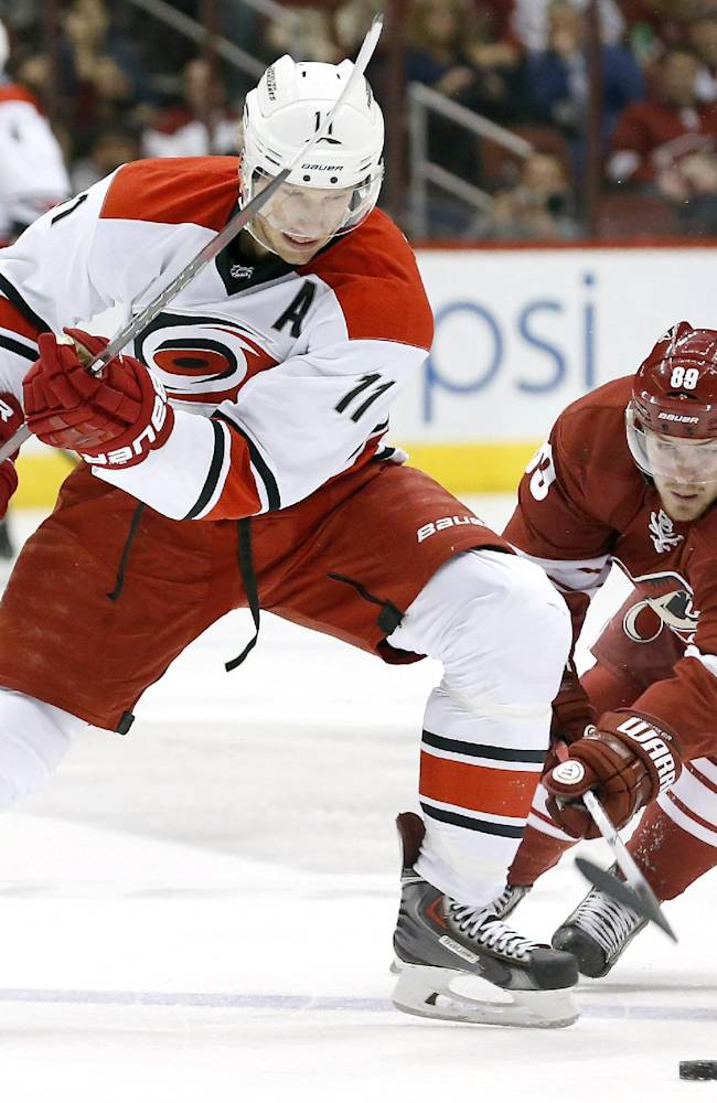 Carolina Hurricanes' Jordan Staal (11) battles Phoenix Coyotes' Mikkel Boedker (89), of Denmark, for the puck during the first period of an NHL hockey game, Saturday, Dec. 14, 2013, in Glendale, Ariz