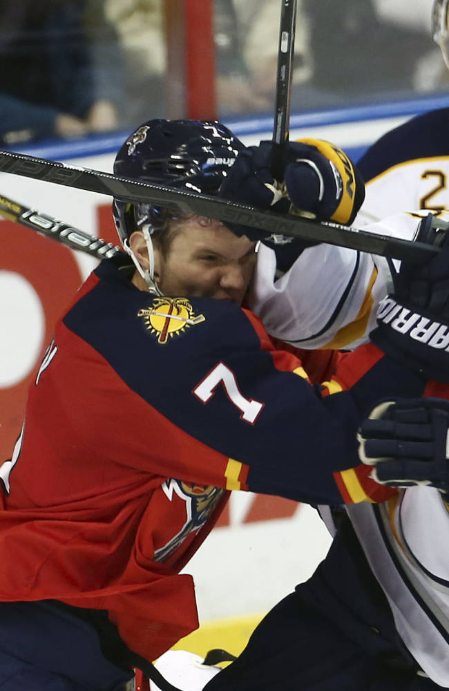 Florida Panthers' Dmitry Kulikov (7) and Buffalo Sabres' Ville Leino (23) collide while chasing the puck during the second period of an NHL hockey game in Sunrise, Fla., Friday, March 7, 2014