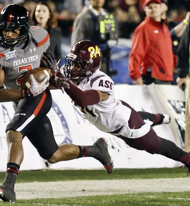 Texas Tech wide receiver Reginald Davis, left, beats Arizona State cornerback Osahon Irabor for a 38-yard pass completion during the first half of the Holiday Bowl NCAA college football game, Monday, Dec. 30, 2013, in San Diego