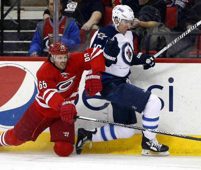 Winnipeg Jets' Blake Wheeler (26) and Carolina Hurricanes' Ron Hainsey (65) collide along the boards during the first period of an NHL hockey game in Raleigh, N.C., Tuesday, Feb. 4, 2014