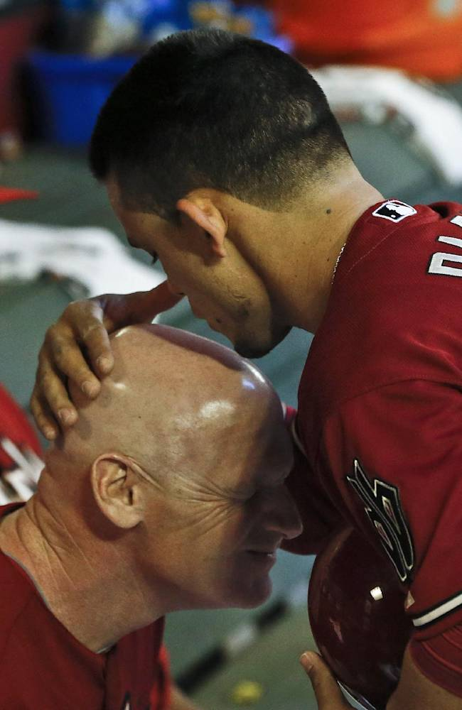 In this May 1, 2013 file photo, Arizona Diamondbacks' Gerardo Parra, right, kisses the head of third base coach Matt Williams in the dugout prior to a baseball game against the San Francisco Giants, in Phoenix.  Williams is the new manager of the Washington Nationals. The Nationals will hold a news conference Friday, Nov. 1, 2013, to introduce Williams as the team's fifth manager since it moved to Washington from Montreal in 2005. He replaces Davey Johnson, who is retiring