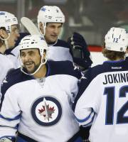 Winnipeg Jets' Dustin Byfuglien, second from left, celebrates his goal with teammates during first period NHL hockey action against the Calgary Flames in Calgary, Canada, Thursday, Jan. 16, 2014. (AP Photo/The Canadian Press, Jeff McIntosh)