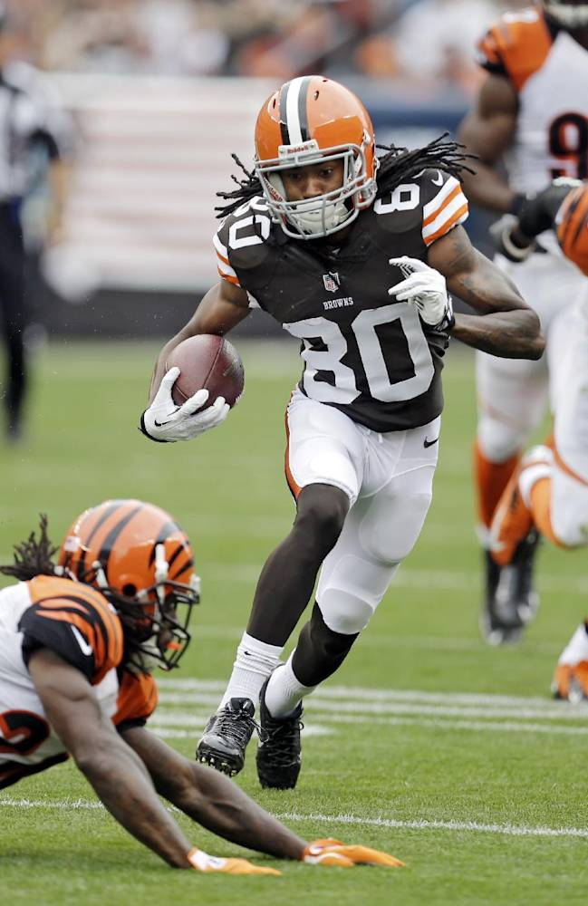Cleveland Browns wide receiver Travis Benjamin (80) avoids Cincinnati Bengals cornerback Adam Jones on a 39-yard pass reception in the first quarter of an NFL football game on Sunday, Sept. 29, 2013, in Cleveland