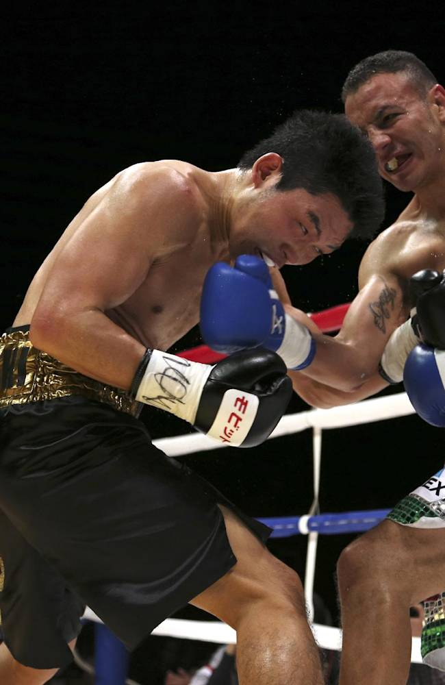Japanese champion Takashi Miura, left, and Mexican challenger Dante Jardon exchange punches in the fourth round of their WBC super featherweight title bout in Tokyo Tuesday, Dec. 31, 2013. Miura defended his title by a technical knockout in the ninth round