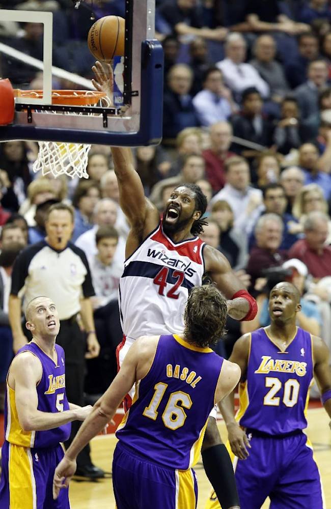 Washington Wizards forward Nene (42), from Brazil, shoots between Los Angeles Lakers guard Steve Blake (5), center Pau Gasol (16), from Spain, and guard Jodie Meeks (20) in the second half of an NBA basketball game Tuesday, Nov. 26, 2013, in Washington. Nene had 30 points and the Wizards won 116-111