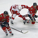 Chicago Blackhawks' Brent Seabrook passes to Marian Hossa, left, as Detroit Red Wings' Andrej Nestrasil, center, checks Seabrook during the third period as the Blackhawks beat the Red Wings 2-1 in overtime in an NHL exhibition hockey game in Chicago on Tu