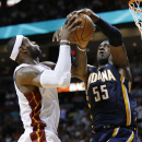 Miami Heat's LeBron James, left, goes up to shoot as Indiana Pacers' Roy Hibbert (55) defends during the second half of an NBA basketball game, Friday, April 11, 2014, in Miami. The Heat defeated the Pacers 98-86. (AP Photo/Lynne Sladky)