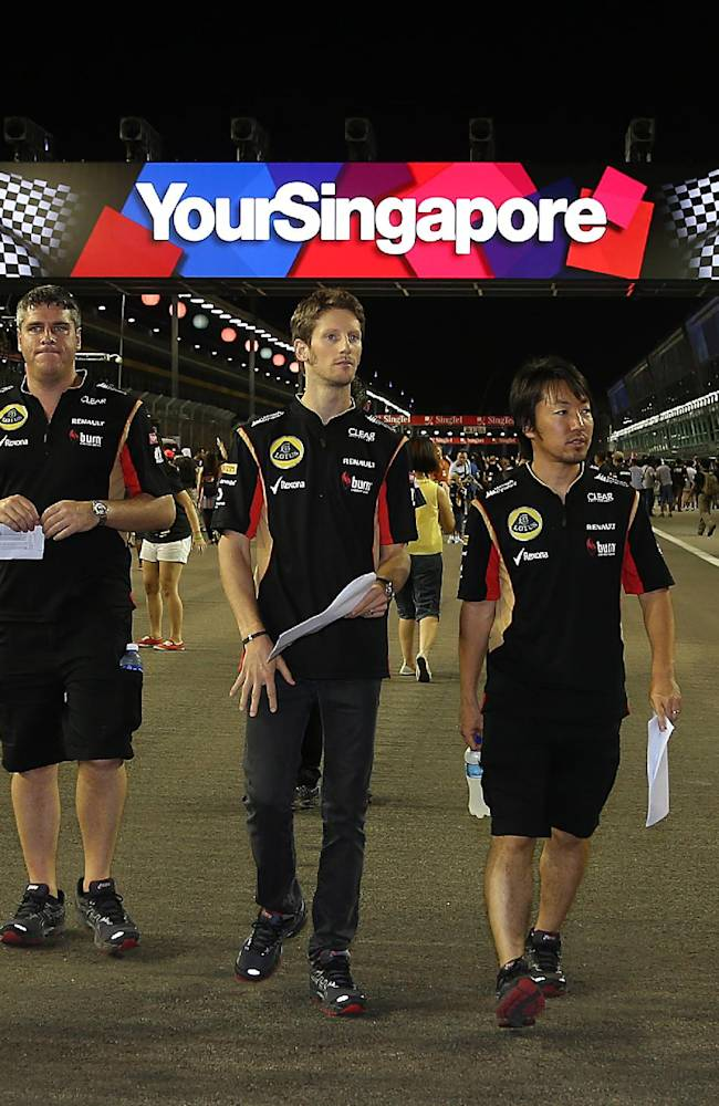 Lotus driver Romain Grosjean of France, centre, walks on the Marina Bay Circuit on Thursday, Sept. 19, 2013, in Singapore, ahead of the Formula One Singapore Grand Prix to be held Sunday Sept. 22, in the city-state
