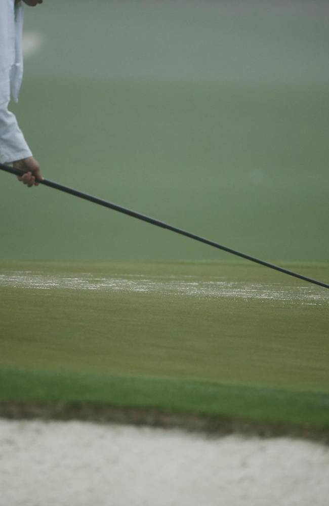 A course worker whips sand off of a practice green during a practice session for the Masters golf tournament Monday, April 7, 2014, in Augusta, Ga